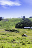 A Hut By A Hill. The slopes of a ski resort are quite empty in the summertime. Wonder why stock images