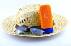 Hut mit Sonnenbrille und Körperlotion Stockfoto