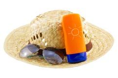 Hut mit Sonnenbrille und Körperlotion auf weißem Hintergrund Stockfotografie
