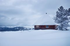 Hut in the mountains in the snow. Winter forest in the snow and Hut in the mountains Stock Photo