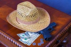 Hut, Pistole und Geld Stockfotografie