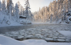 A hut beside a pond. A photo of a hut beside large bond full of ice circles. The hut, land and trees are covered with snow. Water is slightly steaming because it Royalty Free Stock Images