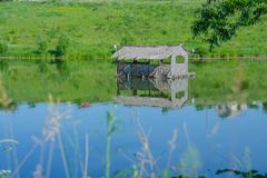 Hut on the pond Stock Images