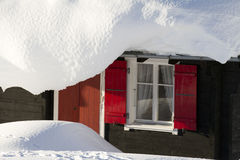 Hut with red shutters in deep snow. The snow is over 1 meter deep. The hut is covered in snow. The sun just rose and the red shutters of this hut make a great Royalty Free Stock Photo