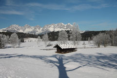 Hut with reflection of tree in snow, Kitzbuhel royalty free stock photography