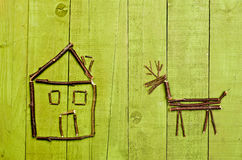 Hut and reindeer arranged from sticks on wooden green backgraund. Stock Photo