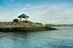 Hut on a rock in the middle of the sea. Hut on a rocky outcrop in the middle of the sea. The blue water and sky make this a perfect place to spend a relaxing day Stock Image