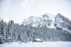A hut in a snowy field with rocky mountains and a forest royalty free stock photography
