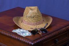 Hut, Sonnenbrille, Geld und Stift Stockfotografie
