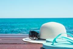 Hut-Sonnenbrille-Pantoffel auf blauer Himmel-und Türkis-Seehintergrund Sommer-Urlaubsreise-Entspannung Idyllischer Meerblick stockbild