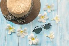 Hut, Sonnenbrillen und Blume auf hölzernem Hintergrund Stockfotos