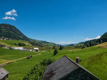 Hut in the Swiss mountains with a meadow and road Royalty Free Stock Photography