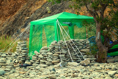 Hut with a tent on a wild beach among the rocks Stock Image