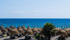 Hut umbrellas on the beach, sea on background, Tenerife Royalty Free Stock Photo