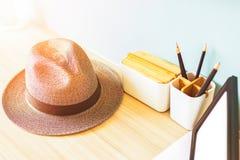 Hut- und Bleistiftkasten sind auf der hölzernen Tabelle Lizenzfreie Stockfotos