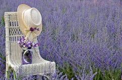 Hut und Glas auf geflochtenem Stuhl Stockfotos