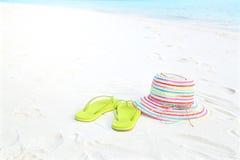 Hut und Pantoffel auf dem Strand Stockbild