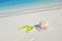 Hut und Pantoffel auf dem Strand Stockbilder