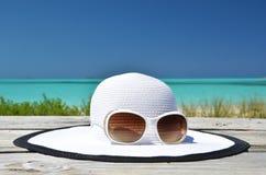 Hut und Sonnenbrille auf dem Strand Stockfoto