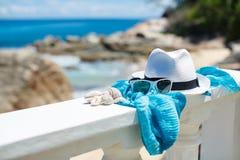 Hut und Sonnenbrille auf Hintergrund von Ozean setzt auf den Strand Lizenzfreies Stockbild