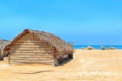 Hut van palmbladen op het strand tegen de achtergrond van slavenboten stock afbeeldingen
