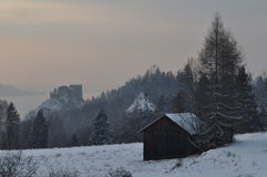 A Hut in a Winter Landscape. A hut in a frosty weather in mountains near medieval castle ruins in evening Royalty Free Stock Photo