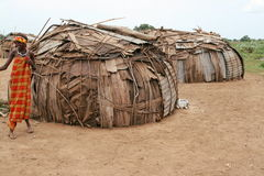 Huts in Lower Omo Valley in Southern Ethiopia. A girl stands near her hut in a village near Omorate in Southern Ethiopia. People from Lower Omo Valley often use Stock Photos