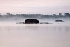 Huts on a misty lake Stock Photography