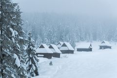 Mountain huts covered with snow in foggy winter scenery Royalty Free Stock Image