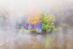 Huts next to small pond on a foggy day. Foggy morning on a small fidhing pond Royalty Free Stock Photography