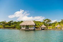 Huts on sea shore in guatemala, santo tomas. Houses of wood and grass on tropical beach on sunny blue sky. Summer vacation on isla. Nd. Wanderlust, adventure and Royalty Free Stock Photo
