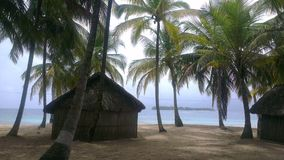 Huts and some coconut trees in a lonely island Royalty Free Stock Photos
