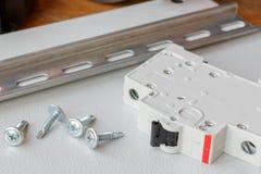 Hutschiene, Leistungsschalter und die Schrauben an der Montageplatte Lizenzfreies Stockbild