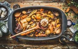 Hutspot met geroosterde groenten, bospaddestoelen en wilde de jachtkip in het koken van pot met houten lepel Konijnragoût op rust Stock Fotografie