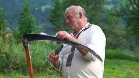 Hutsul in traditional ukrainian clothes sharpening a scythe. Farmer on nature background stock video footage