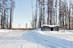 Hutte abandonnée d'hiver sur le chemin forestier d'hiver Photographie stock