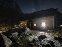 Hutte alpine à la nuit avec et à la manière laiteuse au-dessus de son toit photo libre de droits