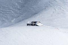 Hutte alpine de montagne d'isolement sur le champ de neige windpacked Images libres de droits
