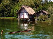 Hutte antique sur des piles à un lac vert Images stock
