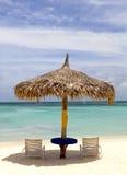 Hutte couverte de chaume sur un bout droit de plage dans Aruba Photographie stock libre de droits