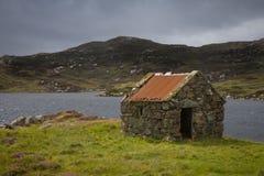 Hutte de Crofters à côté d'un loch Photos stock