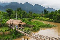 Hutte de village près de rivière dans le vangvieng Laos image stock