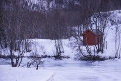 Hutte rouge dans le paysage norvégien neigeux Photo libre de droits