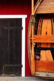 Hutte rouge de pêche avec la porte noire et le bateau en bois Images libres de droits