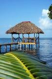 Hutte tropicale au-dessus de l'eau avec le toit couvert de chaume Photo libre de droits