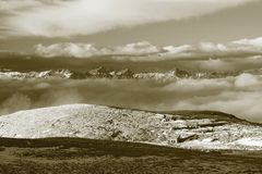 Hutten bij pieken van de heuvel van Alpen, scherpe rotsachtige bergen bij horizon Zonnige de winterdag Bevroren grasspriet in gro Stock Afbeelding