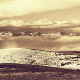 Hutten bij pieken van de heuvel van Alpen, scherpe rotsachtige bergen bij horizon Zonnige de winterdag Bevroren grasspriet in gro Royalty-vrije Stock Foto's