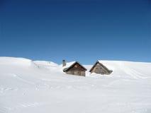 Hutten in diepe sneeuw op de Alpen met exemplaar-ruimte stock foto