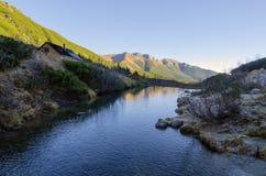 Hutten en rivier in bergen Stock Fotografie