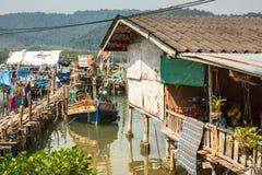 Hutten en vissersboot bij de pijler binnen bij vissersdorp Stock Afbeelding